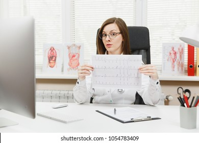 Young female doctor sitting at desk with medical documents, electrocardiogram record, heart ekg cardiogram chart of wave in paper in light office in hospital. Woman in medical gown in consulting room