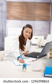 Young female doctor sitting at desk in doctors office using computer, working.