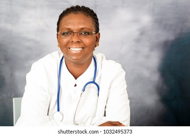 a young female doctor sitting in her office wearing glasses with stethoscope on her neck and smiling at the camera.