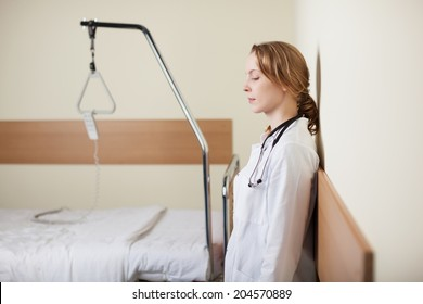 Young female doctor standing with closed eyes leaning against the wall in a ward alongside an empty hospital bed as she takes a moment to gather herself together