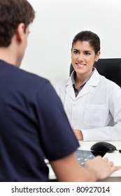 Young female doctor talking to the patient in her office