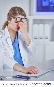 Young female doctor tired after working with computer