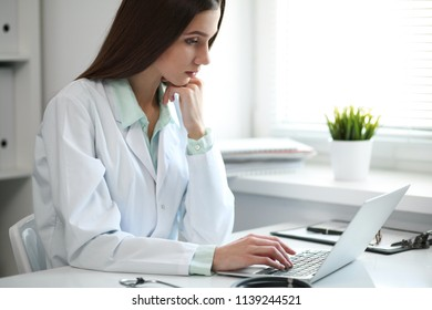 Young female doctor typing on laptop computer while sitting at the table near the window in hospital office