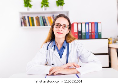 Young female doctor in uniform in doctor's ofice writting a document and look at camera