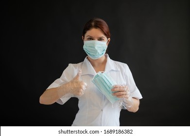 A young female doctor in uniform holds a medical mask on a black background. Nurse shows thumb ok. Coronovirus protection.