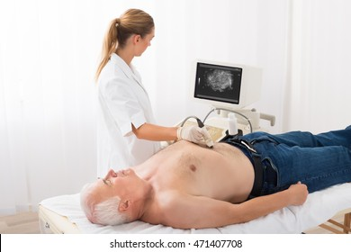 Young Female Doctor Using Ultrasound Scan On Abdomen Of Senior Male Patient In Clinic