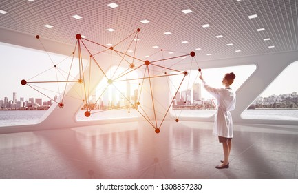Young female doctor in white medical uniform working with social network structure while standing inside white hospital office. Medical industry and contemporary technologies