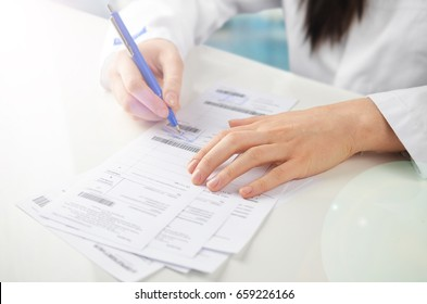 Young female doctor writing a prescription.
