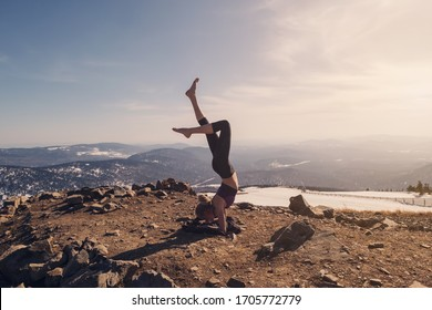 Young female doing headstand yoga exercise on mountain top in beautiful landscape. Sunny winter day