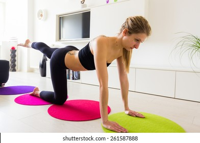 Young female doing her leg raise exercise in her living room.