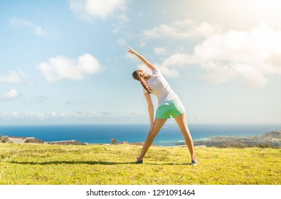 Young female doing streching exercise outdoors.