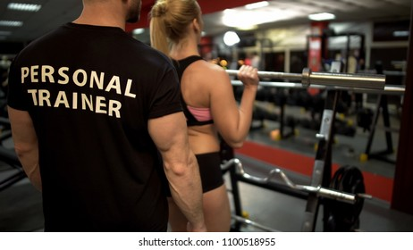 Young female doing weight bar lifting exercise under control of her trainer
