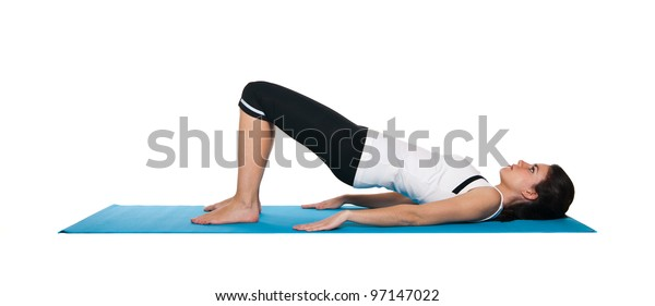 Young female doing workout and exercising on a blue matt. Isolated on white.