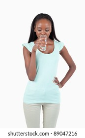 Young female drinking water against a white background