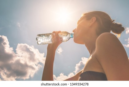 Young female drinking water on a hot summer day.