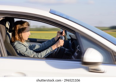 Young Female Driver Driving a White Car on the Road with Focused Facial Expression.
