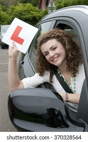 Young female driver holding L learner plate celebrating a pass rating