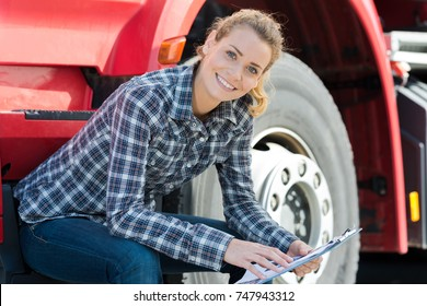 young female driver next to a modern truck