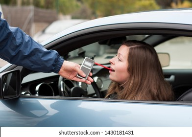 Young female driver not arguing with a police officer during test for alcohol content with breathalyzer, she is calm and willing to cooperate with police officer