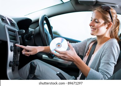 Young female driver playing music in the car - changing CDs (color toned image; shallow DOF)