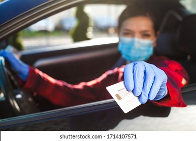 Young female driver showing Coronavirus health card ID immunity passport,proof that a person has developed resilience,COVID-19 risk free certificate,hand holding identification through car window