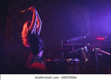 Young female drummer playing drum kit on illuminated stage in nightclub