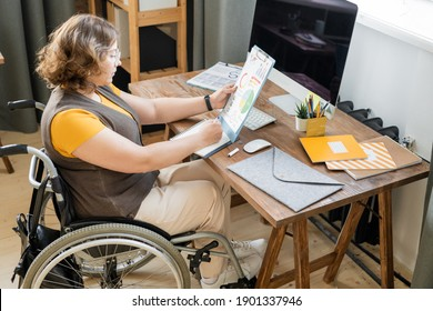 Young female economist in casualwear sitting in wheelchair in front of computer monitor and making notes while analyzing financial data