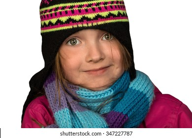 Young female elementary aged child smiling, Dressed for Winter weather, in hat, scarf and jacket