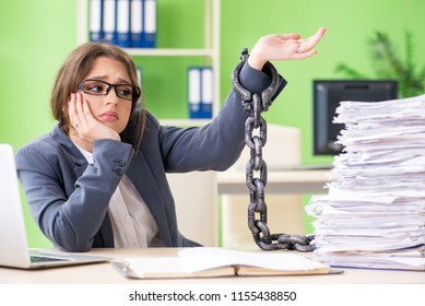 Young female employee  busy with ongoing paperwork chained to th