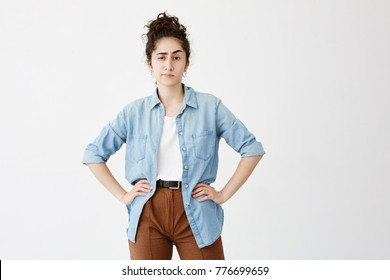 Young female employee resting at home after work. Pretty student girl with dark curly hair in bun, dressed casually waiting for her friends, standing with hands on hips against white background