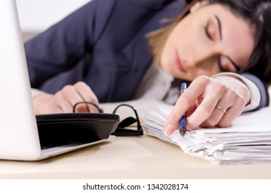 Young female employee sleeping in the office