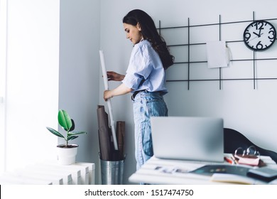 Young female employee taking roll of craft paper. attractive young dark haired female freelancer in jeans and t shirt standing by wall and taking roll of long craft paper from stainless bucket