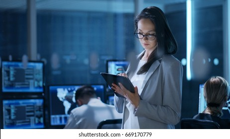 Young Female Engineer Uses Tablet in System Control Center. In the Background Her Coworkers are at Their Workspaces with many Displays Showing Valuable Data.