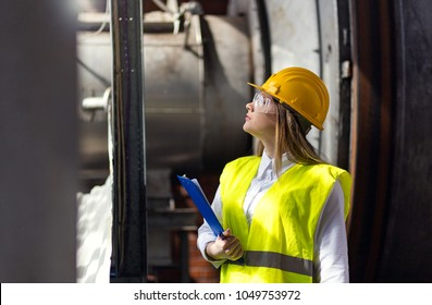 Young female engineer using clipboard.Female quality inspector at factory