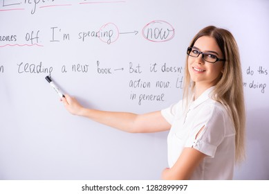 Young female english language teacher standing in front of the b