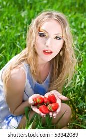 Young female enjoying a fresh strawberry outside