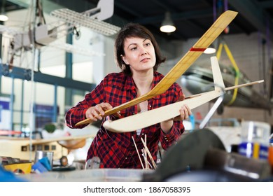 Young female enjoying her hobby - creating light airplanes in aircraft hangar