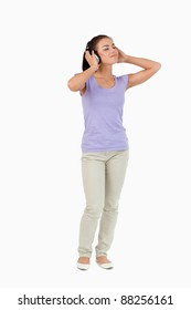 Young female enjoying music with headphones on against a white background