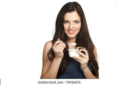 Young female enjoying taste of yogurt isolated on white
