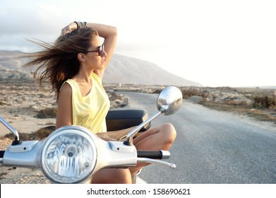 Young female enjoys a motorcycle trip and admires the view
