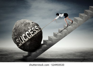 Young female entrepreneur climbing a stairs while pulling a boulder with success word
