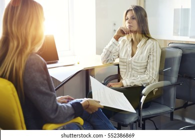 Young female entrepreneur listening to idea of improvement marketing strategy in advertising discussing ideas during personal meeting in coworking office with laptop computer and wireless connection