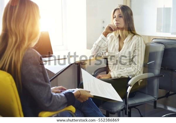 Junge Unternehmerinnen, die sich Gedanken über eine Verbesserung der Marketingstrategie bei der Diskussion von Ideen während der persönlichen Besprechung in einem Büro mit Laptop-Computer und Wireless-Verbindung in der Zusammenarbeit mit Laptop-und Wireless-Verbindung