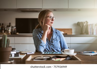 Young female entrepreneur looking through a window while working at a table in her kitchen at home