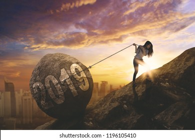 Young female entrepreneur pulling number 2019 in a stone with  while walking on the cliff. Shot at sunset time