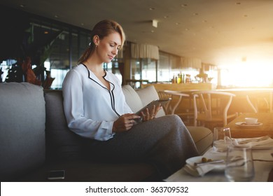 Young female entrepreneur reading electronic book on digital tablet during lunch in modern restaurant interior, elegant businesswoman chatting on touch pad while sitting in comfortable coffee shop
