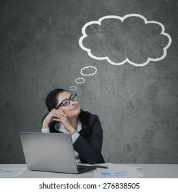 Young female entrepreneur working with laptop while daydreaming and looking at cloud tag