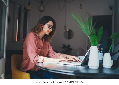 Young female entrepreneur working remotely from a home office using modern laptop computer, woman copywriter working online