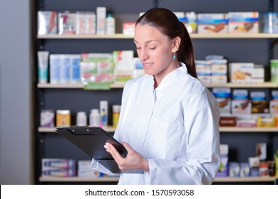Young female expert pharmacist is making notes while standing