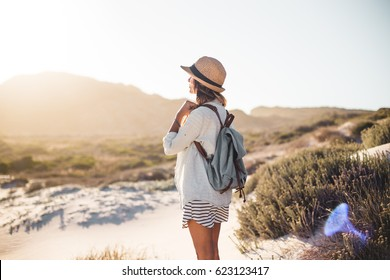 Young female exploring sandy beach with hat and backpack